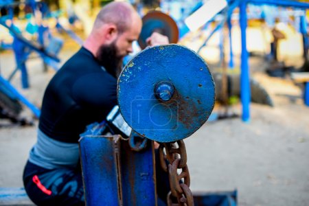 Photo for Side view of man in sportswear during workout in outdoor gym. Focus on barbell. - Royalty Free Image