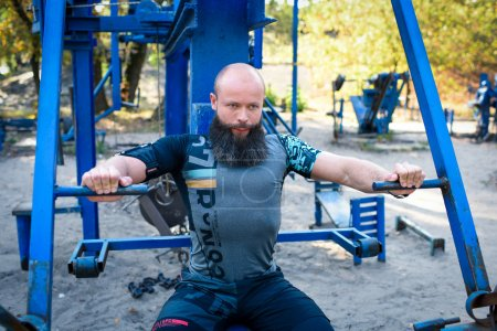 Photo for Active man doing exercises for chest on equipment in outdoor gym - Royalty Free Image