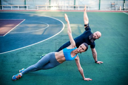 Sporty couple doing side plank
