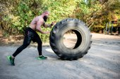 Bearded man exercising with tractor tire