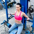 Muscular woman training on equipment and doing exe...