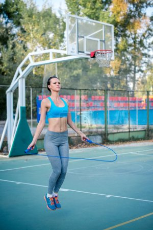 Active woman jumping with skipping rope