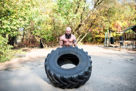 Photo for A strong man lifting a large tractor tire in outdoor gym - Royalty Free Image