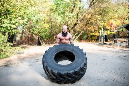 Photo pour Un homme fort, soulever un pneu de tracteur gros dans la salle de gym en plein air - image libre de droit