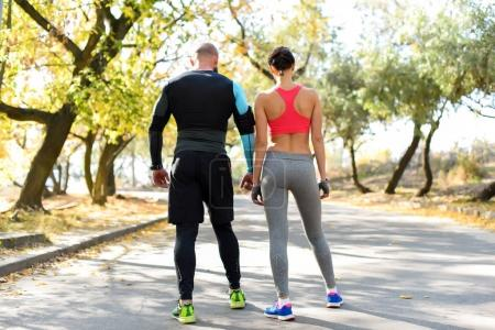 Photo for Rear view of sportive couple standing on road outdoors - Royalty Free Image
