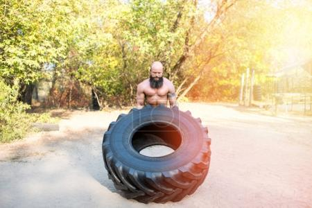 sportsman exercising with tire