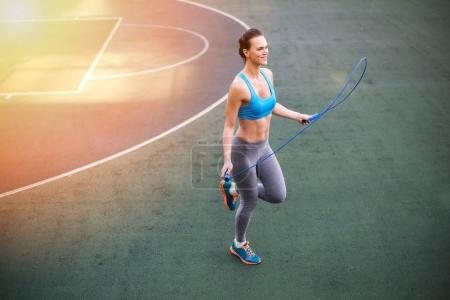 Photo for Smiling young woman in sportswear exercising with skipping rope on stadium - Royalty Free Image