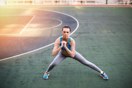 Photo for Young sporty woman in sportswear exercising on stadium at sunset - Royalty Free Image
