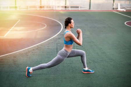 Photo for Side view of young sporty woman in sportswear exercising on stadium - Royalty Free Image