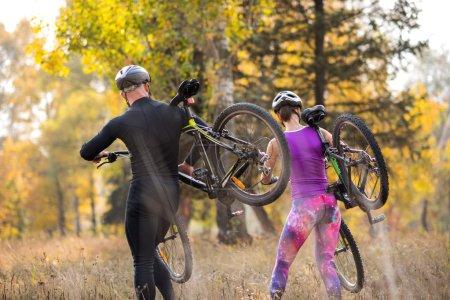 Photo pour Deux cyclistes portant leurs vélos en faisant de l'exercice dans le parc - image libre de droit