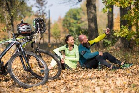 Photo pour Couple de cyclistes prenant selfie tout en étant assis et se reposant dans le parc d'automne, vélos au premier plan - image libre de droit
