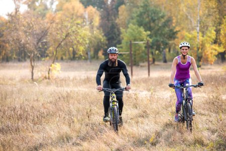 Photo for Adult couple cycling outdoors in beautiful autumn park - Royalty Free Image