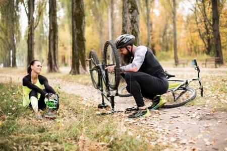 Photo pour Homme adulte réparer vélo tandis que sa petite amie assis sur l'herbe et se reposant dans le parc d'automne - image libre de droit