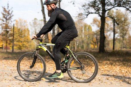 Photo pour Adulte homme barbu automne parc à vélo - image libre de droit
