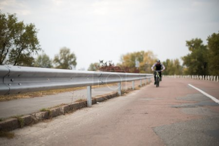 Photo for People cycling on road along barrier - Royalty Free Image