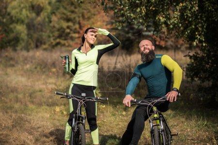 Photo pour Couple de cyclistes se reposer pendant leur voyage de vélo dans le parc automne - image libre de droit