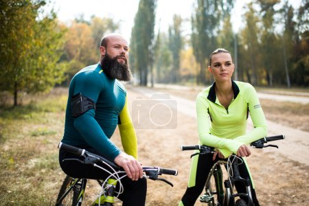Couple of cyclists in autumn park