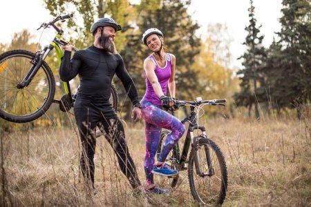 Photo pour Couple adulte faisant du vélo en plein air dans un magnifique parc d'automne - image libre de droit