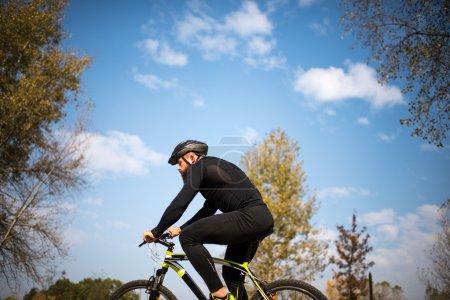 Photo pour Homme barbu adulte faisant du vélo dans un parc d'automne - image libre de droit