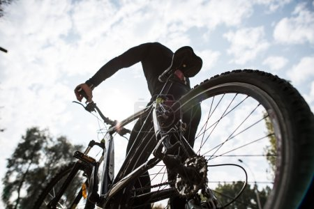 Photo pour Angle bas, vue arrière de l'homme avec vélo sur fond de nature d'automne flou - image libre de droit