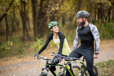 Photo pour Couple de cyclistes permanent avec les vélos en automne parc - image libre de droit