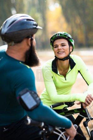 Photo pour Couple de cyclistes se reposant pendant leur voyage à vélo dans le parc d'automne - image libre de droit
