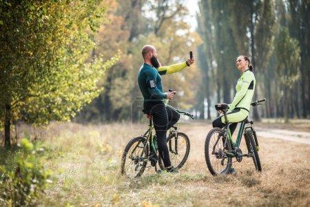 Foto de Foto de toma de ciclista barbudo de niña mientras que permanente con bicicletas en el Parque otoño - Imagen libre de derechos