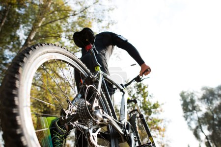 Photo for Low angle, rear view of man with bicycle on blurred autumn nature background - Royalty Free Image
