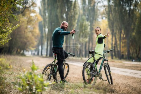 Photo for Couple of cyclists resting during their cycling journey in autumn park - Royalty Free Image