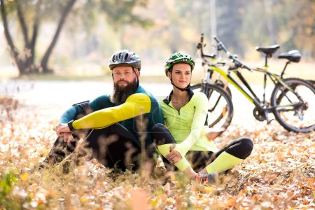 cyclists resting on dry autumn lawn