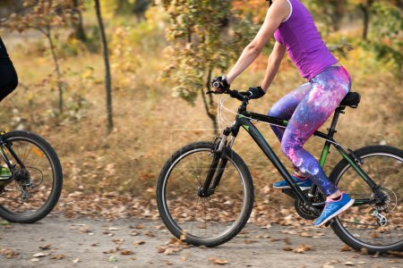 Photo for Young woman cycling in autumn park - Royalty Free Image