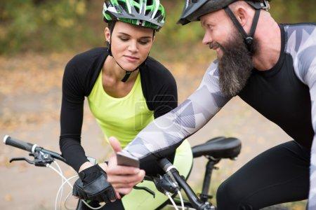 Man cyclist showin smartphone to girl