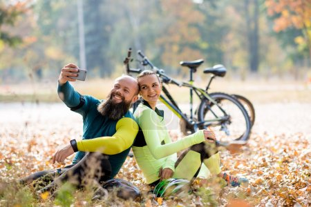 Photo pour Couple of cyclists taking selfie while sitting near their bikes - image libre de droit