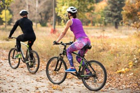 Photo pour Couple de personnes automne parc à vélo - image libre de droit