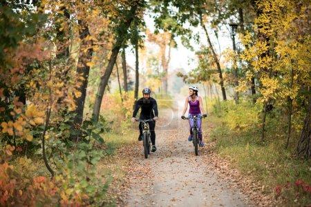 Photo pour Adulte couple cyclisme à l'extérieur dans le magnifique parc automne - image libre de droit