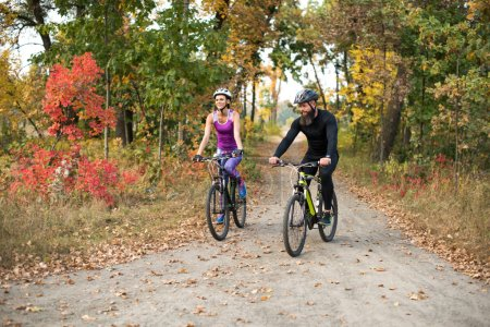 people cycling in autumn park