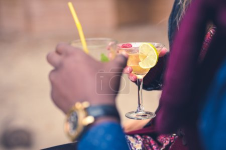 Photo for Close-up hands of young couple holding glasses with cocktails at picnic - Royalty Free Image