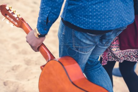 Photo for Close-up side view of man carrying guitar walking with young woman on sandy beach - Royalty Free Image