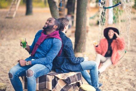 Foto de Feliz sonriente a joven amigos celebración de cócteles y la diversión en picnic al aire libre en playa - Imagen libre de derechos