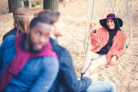 Fashionable woman in net swing with friends