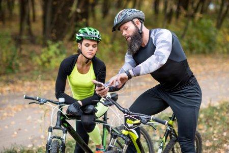 Photo pour Homme barbu montrant smartphone à la jeune fille tout en se tenant debout avec des vélos dans le parc d'automne - image libre de droit