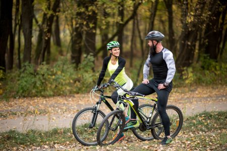 Photo for Couple of cyclists standing with bikes and looking at each other in autumn park - Royalty Free Image