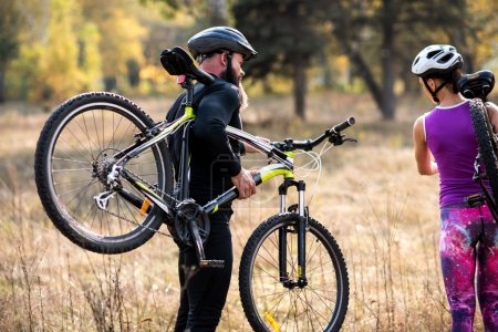 Photo for Two cyclists carrying bikes while exercising in autumn park - Royalty Free Image