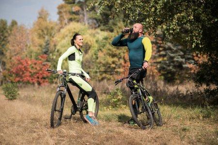 Foto de Pareja de ciclistas descansando durante el viaje de ciclismo en el Parque otoño - Imagen libre de derechos