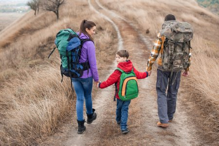 Photo for Back view of young family with backpacks walking on rural path at cloudy autumn day - Royalty Free Image