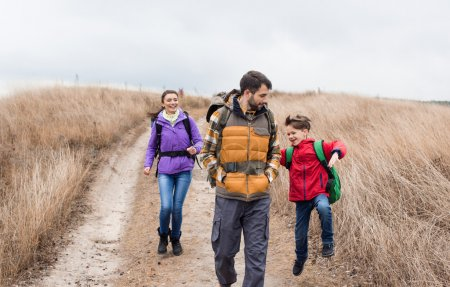 Happy family with backpacks walking