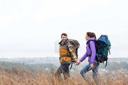 Photo for Young smiling couple with backpacks holding hands and walking in tall grass in rural area - Royalty Free Image
