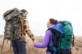 Young couple with backpacks holding hands