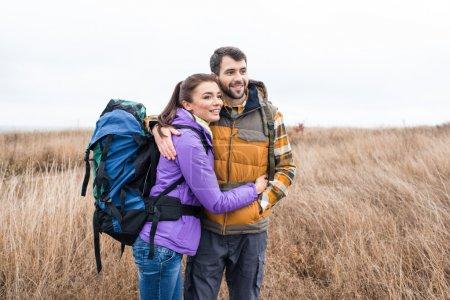 Photo pour Heureux jeune couple avec sacs à dos debout embrassant dans les hautes herbes sèches à jour nuageux de l'automne - image libre de droit
