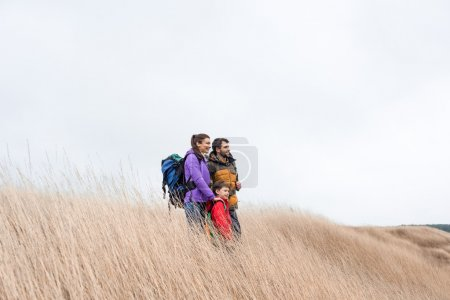 Happy family with backpacks standing in grass
